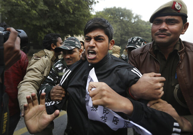 Policemen detain students protesting outside Uttar Pradesh Bhawan during a protest against a new citizenship law and violence by police in the state, in New Delhi, India, Friday, Dec. 27, 2019. The new citizenship law allows Hindus, Christians and other religious minorities who are in India illegally to become citizens if they can show they were persecuted because of their religion in Muslim-majority Bangladesh, Pakistan and Afghanistan. It does not apply to Muslims. (AP Photo/Manish Swarup)