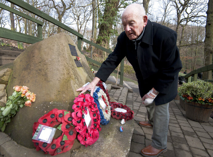 Tony Foulds tends to a memorial honouring 10 U.S. airmen who died in a plane crash in Endcliffe Park, Sheffield, England, Wednesday, Feb. 13, 2019. Foulds was just a kid running around in the park on Feb. 22, 1944 when a U.S. Air Force crew decided to crash and die rather than take the chance of hitting them. He's dreamed of honoring them for decades. Now he's 82 and about to get his wish. (AP Photo/Rui Vieira)