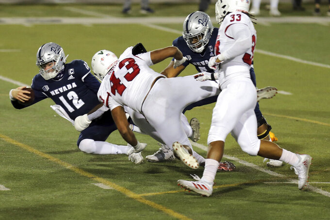 Nevada quarterback Carson Strong (12) is tackled by the Fresno State defense during the second halfof an NCAA college football game Saturday, Dec. 5, 2020, in Reno, Nev. (AP Photo/Lance Iversen)