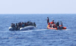 In this photo taken Saturday and released Sunday, Aug. 11, 2019, a rescue team of the Ocean Viking ship, operated by the NGOs Sos Mediterranee and Doctors Without Borders, approaches a rubber dinghy with over 80 migrants off the Libyan coast. The Ocean Viking was already carrying over 80 people rescued earlier, and is blocked at sea while it waits to be assigned a safe port. Italian Interior Minister Matteo Salvini, who has triggered a government crisis in Italy, signed Friday a ban on the ship's entry into Italian waters. (Hannah Wallace Bowman/MSF/Sos Mediterranee via AP)