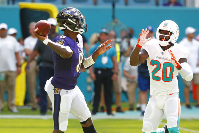 Baltimore Ravens quarterback Lamar Jackson (8) looks to pass, as Miami Dolphins free safety Reshad Jones (20) attempts to defend, during the second half at an NFL football game, Sunday, Sept. 8, 2019, in Miami Gardens, Fla. (AP Photo/Wilfredo Lee)
