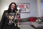 In this Thursday, Jan. 31, 2019, photo Lisa Topol poses for a photo with her two rescue dogs, Schmutzy, right, and Plop, in New York. Topol recently had the DNA tested for both dogs. Genetic testing for dogs has grown rapidly in recent years, fueled by companies marketing kits that offer to decode dogs' heritage and health as simply, or laboriously, as owners can swab a canine cheek. More than a million dogs have been tested in little over a decade. (AP Photo/Mary Altaffer)