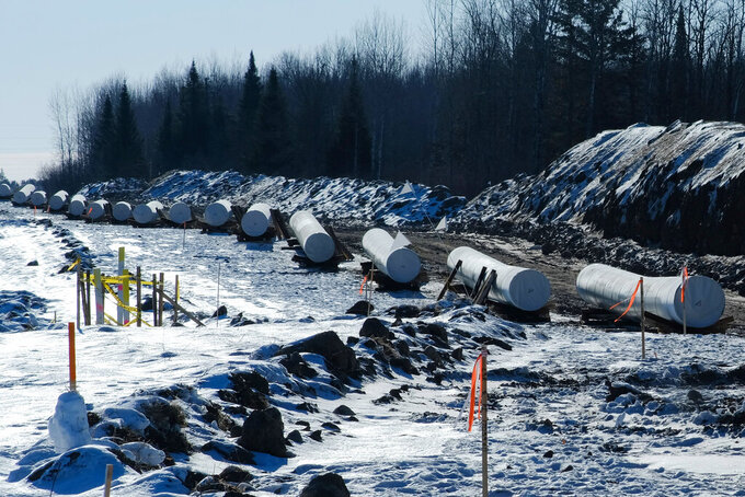 Sections of pipe await placement near Grand Rapids, Minnesota, for the Enbridge Line 3 project on Feb. 8, 2021. Conflict is growing among Indigenous communities along the nearly 400-mile path of Enbridge's Line 3. As the project cuts across the Fond du Lac reservation, treaty lands of several other bands of Ojibwe, and the headwaters of the Mississippi River in northern Minnesota, it has brought not just jobs but controversy and discord into the most intimate spheres of spirituality, family, and community. (Mary Annette Pember/Indian Country Today via AP)