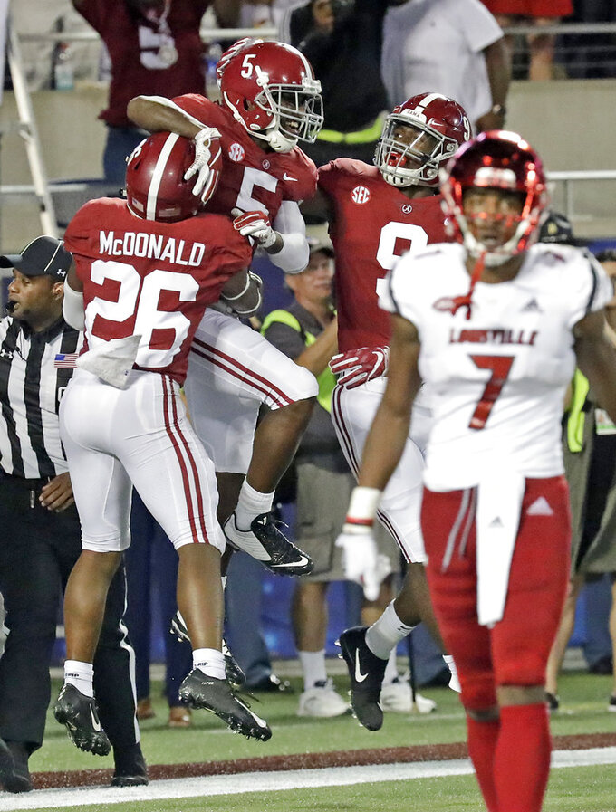 FILE - In this Sept. 1, 2018, file photo, Alabama defensive back Shyheim Carter (5) celebrates with Kyriq McDonald (26) and Eyabi Anoma (9) after returning an interception 45-yards for a touchdown, as Louisville wide receiver Dez Fitzpatrick (7) walks off the field, during the second half of an NCAA college football game in Orlando, Fla. Alabama's defense, for a change, has been overshadowed by the offense, but it's still formidable. (AP Photo/John Raoux, File)