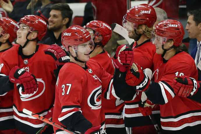 Carolina Hurricanes right wing Andrei Svechnikov (37), of Russia, celebrates with teammates following Svechnikov's goal against the Calgary Flames during the third period of an NHL hockey game in Raleigh, N.C., Tuesday, Oct. 29, 2019. Carolina won 2-1. (AP Photo/Gerry Broome)