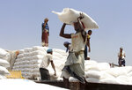 FILE - In this Sept. 21, 2018 file photo, men deliver U.N. World Food Programme (WFP) aid in Aslam, Hajjah, Yemen. Houthi rebels in Yemen have blocked half of the United Nations' aid delivery programs in the war-torn country — a strong-arm tactic to force the agency to give them greater control over the massive humanitarian campaign, along with a cut of billions of dollars in foreign assistance, according to aid officials and internal documents obtained by The Associated Press. (AP Photo/Hammadi Issa, File)