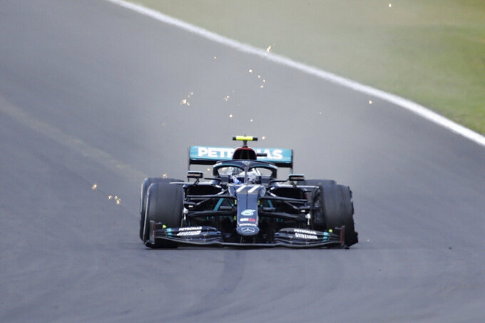 Mercedes driver Valtteri Bottas of Finland steers his car with a flat tire during the British Formula One Grand Prix at the Silverstone racetrack, Silverstone, England, Sunday, Aug. 2, 2020. (Andrew Boyers/Poolvia AP)