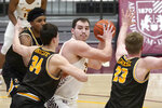 Loyola Chicago's Cameron Krutwig, center, looks to pass as Valparaiso's Jacob Ognacevic (34) and Ben Krikke defend during the second half of an NCAA college basketball game Wednesday, Feb. 17, 2021, in Chicago. Loyola Chicago won 54-52. (AP Photo/Charles Rex Arbogast)