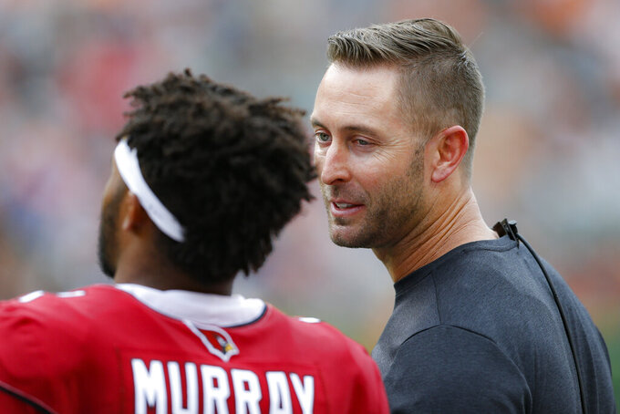 Arizona Cardinals head coach Kliff Kingsbury, right, speaks with quarterback Kyler Murray, left, in the first half of an NFL football game against the Cincinnati Bengals, Sunday, Oct. 6, 2019, in Cincinnati. (AP Photo/Gary Landers)
