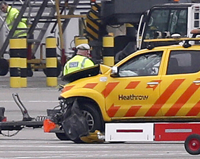 Emergency personnel attend to one of the vehicles involved in a crash at Heathrow Airport, London on Wednesday Feb. 14, 2018. London's Heathrow Airport says two men have been injured after a