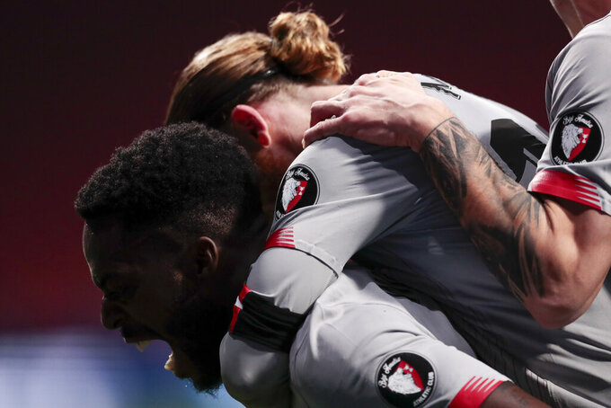 Athletic Bilbao's Iker Muniain, right, celebrates after scoring his side's first goal with his teammate Inaki Williams, left, during the Spanish La Liga soccer match between Atletico Madrid and Athletic Bilbao at Wanda Metropolitano stadium in Madrid, Spain, Wednesday, March 10, 2021. (AP Photo/Bernat Armangue)