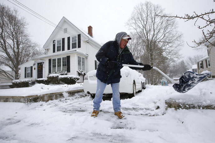 Jerry Drummey shovels a sidewalk Tuesday, Dec. 3, 2019, in Norwood, Mass. The National Weather Service issued a winter storm warning Tuesday for coastal areas of Massachusetts, New Hampshire and Maine and a winter weather advisory for southeastern Massachusetts and Rhode Island. (AP Photo/Steven Senne)