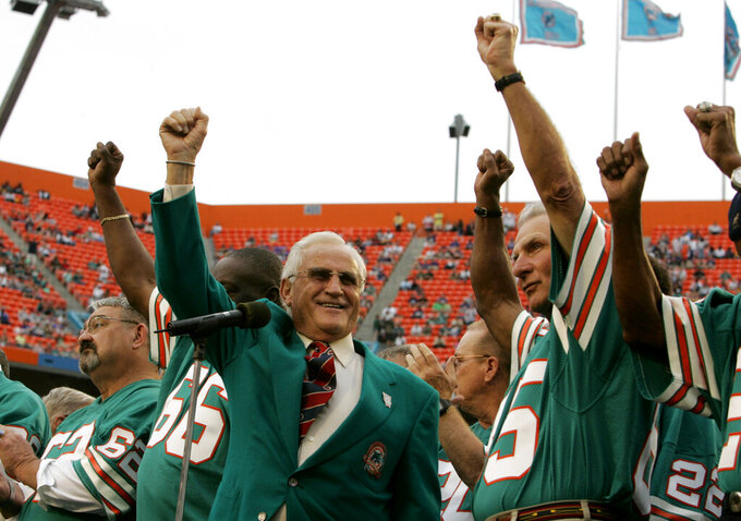 FILE - In this Dec. 16, 2007 file photo, former Miami Dolphins coach Don Shula, left, and player Nick Buoniconti, right, wave during a halftime ceremony honoring the 1972 perfect season of the Dolphins during an NFL football game against the Baltimore Ravens at Dolphin Stadium in Miami. Pro Football Hall of Fame middle linebacker Nick Buoniconti, an undersized overachiever who helped lead the Miami Dolphins to the NFL's only perfect season, has died at the age of 78. Bruce Bobbins, a spokesman for the Buoniconti family, said he died Tuesday, July 30, 2019, in Bridgehampton, N.Y. (AP Photo/Lynne Sladky, File)