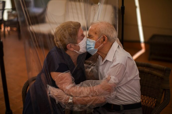 In this Monday, June 22, 2020 photo, Agustina Cañamero, 81, and Pascual Pérez, 84, hug and kiss through a plastic film screen to avoid contracting the new coronavirus at a nursing home in Barcelona, Spain. Even when it comes wrapped in plastic, a hug can convey tenderness and relief, love and devotion. The fear that gripped Agustina Cañamero during the 102 days she and her 84-year-old husband spent physically separated during Spain's coronavirus outbreak dissolved the moment the couple embraced through a screen of plastic film. (AP Photo/Emilio Morenatti)