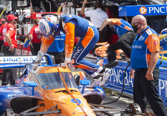 Scott Dixon (9) of New Zealand enters his car before a qualifying run before an IndyCar Series auto race, at Mid-Ohio Sports Car Course, Saturday, Sept. 12, 2020, in Lexington, Ohio. (AP Photo/Phil Long)