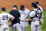New York Yankees manager Aaron Boone, in black, talks with pitcher Michael King, center, before pulling him during the fourth inning of the team's baseball game against the Minnesota Twins on Thursday, June 10, 2021, in Minneapolis. (AP Photo/Jim Mone)