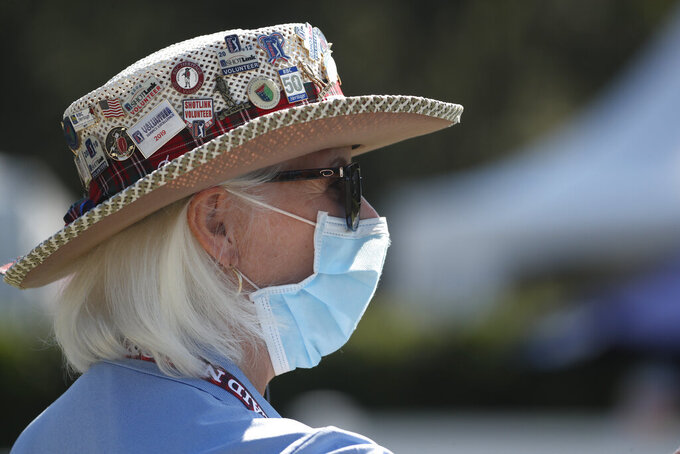 Cheryl Pearce, a volunteer working the first tee, wears a mask as a precaution against the coronavirus, at the start the third round of the RBC Heritage golf tournament, Saturday, June 20, 2020, in Hilton Head Island, S.C. (AP Photo/Gerry Broome) Cheryl Bearce