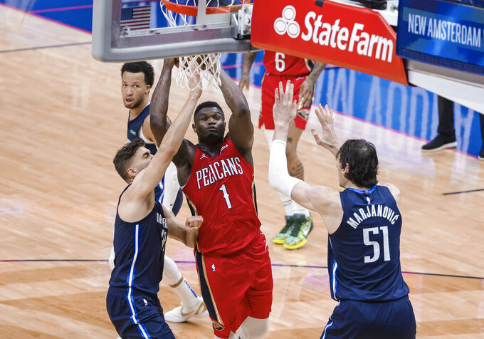 New Orleans Pelicans forward Zion Williamson (1) shoots over Dallas Mavericks forward Maxi Kleber (42) and center Boban Marjanovic (51) in the fourth quarter of an NBA basketball game in New Orleans, Saturday, March 27, 2021. (AP Photo/Derick Hingle)
