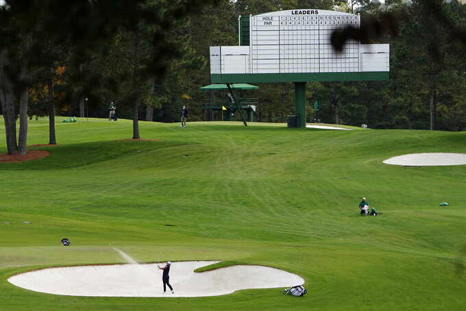 Is Woo Kim, of South Korea, hits out of a bunker on the second hole during a practice round for the Masters golf tournament Monday, Nov. 9, 2020, in Augusta, Ga. (AP Photo/Matt Slocum)