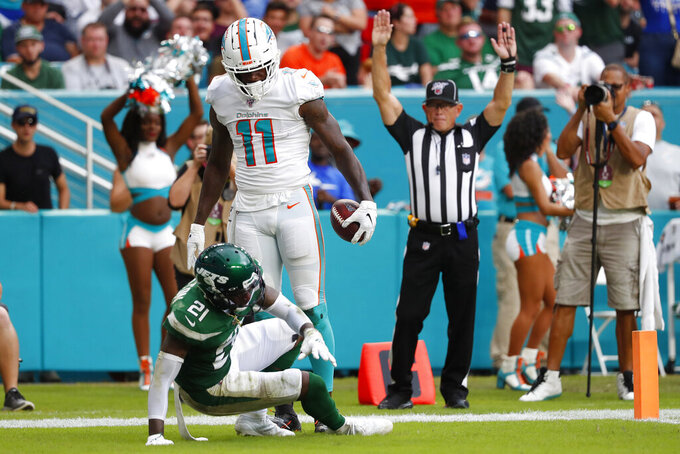 Miami Dolphins wide receiver DeVante Parker (11) looks down at New York Jets cornerback Nate Hairston (21) after scoring a touchdown during the first half of an NFL football game, Sunday, Nov. 3, 2019, in Miami Gardens, Fla. (AP Photo/Wilfredo Lee)