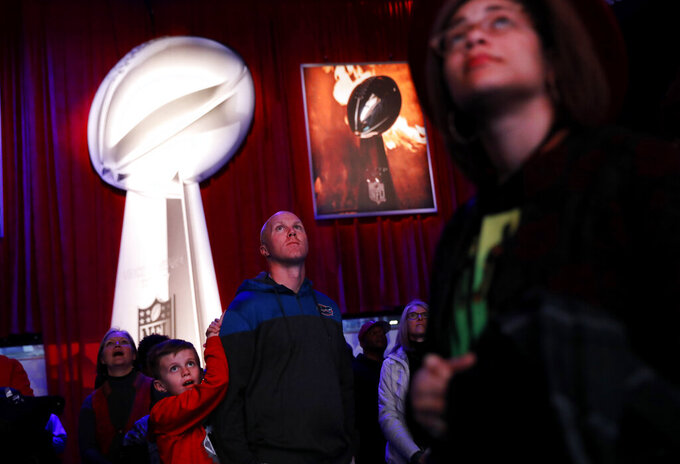 Kyle Williams, right, and his son Grant, 8, of Monroe, Ga., watch a video while waiting in line to see the Vince Lombardi Trophy at the NFL Experience ahead of Sunday's Super Bowl 53 football game between the Los Angeles Rams and New England Patriots in Atlanta, Wednesday, Jan. 30, 2019. (AP Photo/David Goldman)
