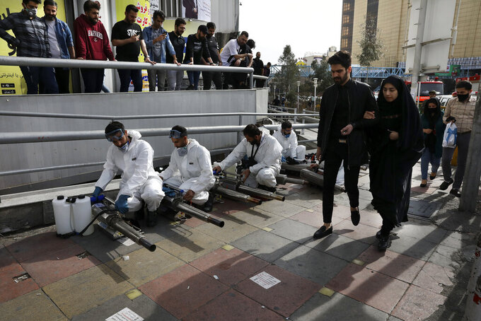 Firefighters prepare their fogging machines to disinfect a street against the new coronavirus as some people watch and pedestrians walk, in western Tehran, Iran, Friday, March 13, 2020. The new coronavirus outbreak has reached Iran's top officials, with its senior vice president, Cabinet ministers, members of parliament, Revolutionary Guard members and Health Ministry officials among those infected. The vast majority of people recover from the new coronavirus. According to the World Health Organization, most people recover in about two to six weeks, depending on the severity of the illness.  (AP Photo/Vahid Salemi)