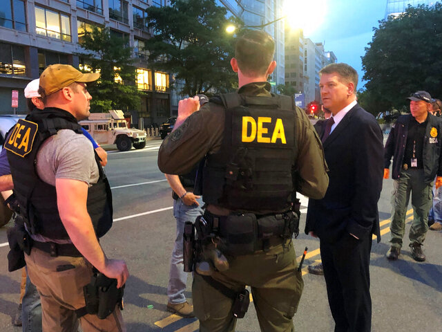 In this Wednesday, June 3, 2020, photo Acting Drug Enforcement Administrator Timothy Shea, right, visits with DEA agents at a checkpoint in Washington. More than 1,500 people have been arrested in the last three months as part of a Drug Enforcement Administration project focusing on violent crime. The initiative, nicknamed Project Safeguard, comes as President Donald Trump has touted similar operations as a much-needed answer to a spike in crime. It's also to showcase what he says is his law-and-order prowess, claiming he's countering rising crime in cities run by Democrats. Acting DEA Administrator Tim Shea tells the AP that since the operation launched in August, 1,521 people have been arrested in both state and federal cases in cities across the U.S. and 2,135 firearms have been seized.   (AP Photo/Mike Balsamo)