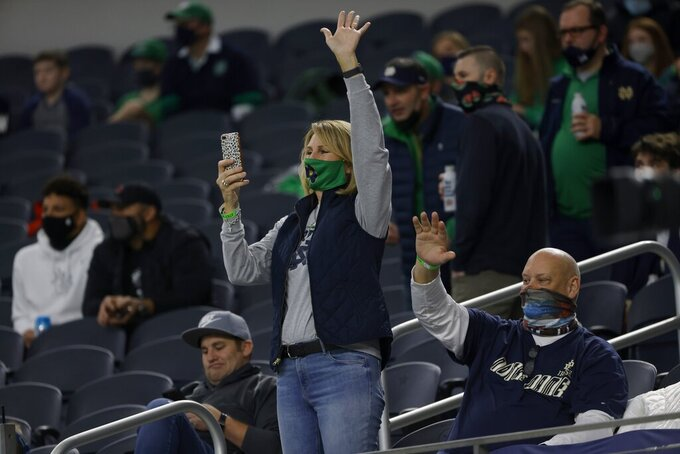 A pair of Notre Dame fans watch warmups before the Rose Bowl NCAA college football game against Alabama in Arlington, Texas, Friday, Jan. 1, 2021. (AP Photo/Ron Jenkins)
