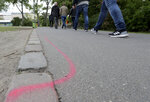 Men walk past a so called 'Drug Dealer Area' next to a traffic training course for kids at the public Goerlitzer Park in Berlin, Germany, Thursday, May 9, 2019. (AP Photo/Michael Sohn)