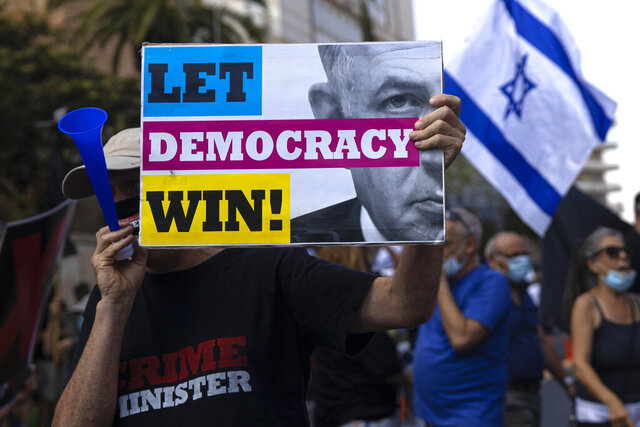 An Israeli protester hold a sign during the