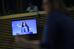 European Trade Commissioner Cecilia Malmstrom, right unfocused, is displayed on a tv screen as she talks to journalists during a news conference at the European Commission headquarters in Brussels, Monday, April 15, 2019. (AP Photo/Francisco Seco)