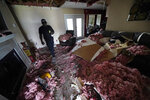 Michael Lathers walks past the collapsed ceiling in his flooded home in the aftermath of Hurricane Ida in LaPlace, La., Tuesday, Sept. 7, 2021. (AP Photo/Gerald Herbert)