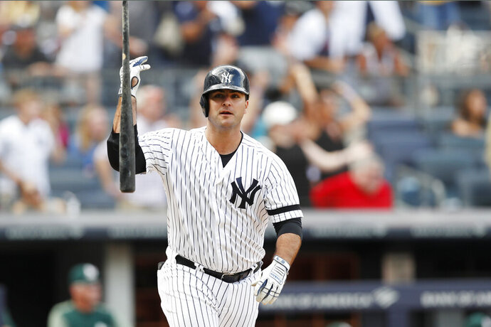 New York Yankees' Mike Ford tosses his after hitting a pinch-hit, walk-off solo home run in the ninth inning of a baseball game against the Oakland Athletics, Sunday, Sept. 1, 2019, in New York. The Yankees won 5-4. (AP Photo/Kathy Willens)