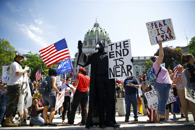 FILE - In this Friday, May 15, 2020 file photo, protesters hold a rally against Pennsylvania's coronavirus stay-at-home order at the state Capitol in Harrisburg, Pa. (AP Photo/Matt Rourke)