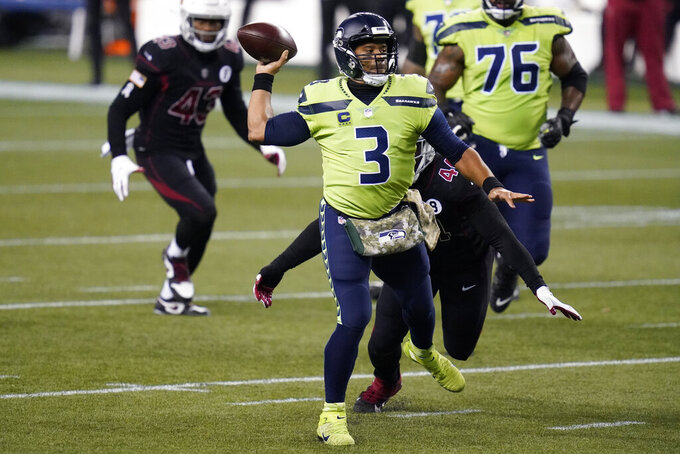 Seattle Seahawks quarterback Russell Wilson passes to DK Metcalf (not shown) for a touchdown during the first half of an NFL football game against the Arizona Cardinals, Thursday, Nov. 19, 2020, in Seattle. (AP Photo/Elaine Thompson)