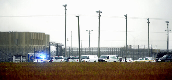 FILE - In this Oct. 12, 2017, file photo, police vehicles are seen outside Pasquotank Correctional Institution in Elizabeth City, N.C. Closing arguments are expected next week in the trial of an inmate accused of murder in a deadly attempted breakout that left four North Carolina prison workers dead. The Virginian-Pilot reports jurors were shown a video interview Thursday, Oct. 17, 2019, in which Mikel Brady described striking a prison guard until she stopped moving during the Oct. 2017 escape attempt at the prison. (Thomas J. Turney/The Daily Advance via AP, File)