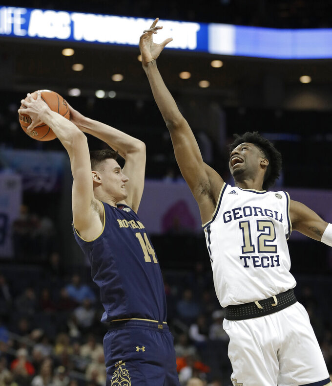 Notre Dame's Nate Laszewski (14) grabs a rebound in front of Georgia Tech's Khalid Moore (12) during the first half of an NCAA college basketball game in the Atlantic Coast Conference tournament in Charlotte, N.C., Tuesday, March 12, 2019. (AP Photo/Nell Redmond)