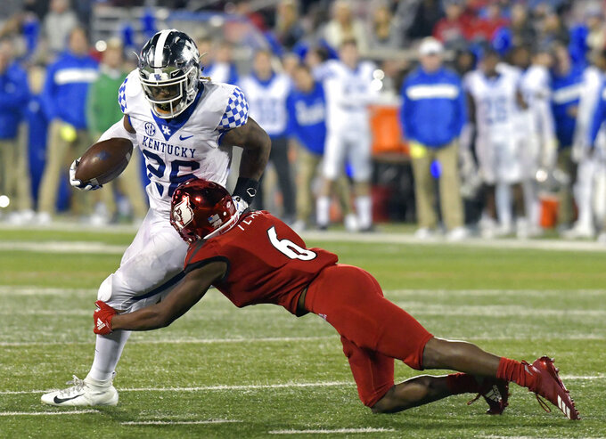 Louisville cornerback Russ Yeast (6) attempts to bring down Kentucky running back Benny Snell Jr. (26) during the first half of an NCAA college football game in Louisville, Ky., Saturday, Nov. 24, 2018. (AP Photo/Timothy D. Easley)
