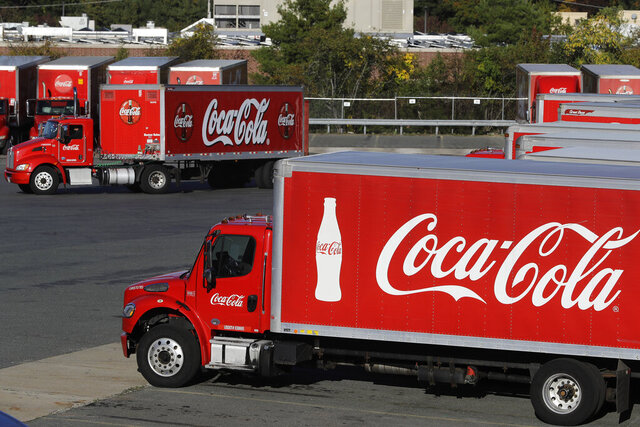FILE - In this Oct. 14, 2019 photo a truck with the Coca-Cola logo, behind left, maneuvers in a parking lot at a bottling plant in Needham, Mass. The Coca-Cola Co. said Thursday, Dec. 17, 2020, it's laying off 2,200 workers, or 17% of its global workforce, as part of a larger restructuring aimed at paring down its business units and brands. (AP Photo/Steven Senne, File)