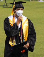 An unidentified graduate puts on his mask after receiving his diploma at the graduation ceremony of Spain Park High School in Hoover, Ala., Wednesday, May 20, 2020. Health officials say usual graduation ceremonies could endanger the public health by promoting the spread of disease. But school officials say they're using social distancing guidelines and abiding by state health rules. (AP Photo/Jay Reeves)