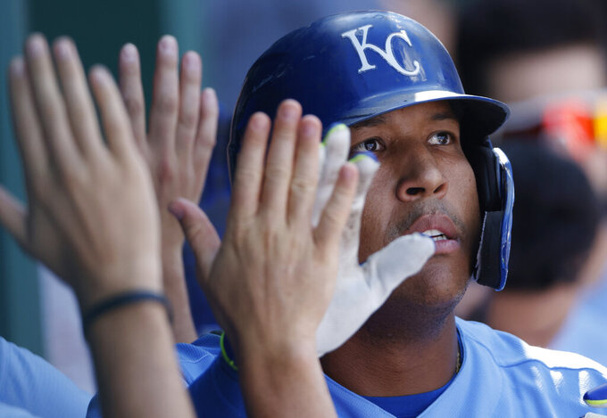 Kansas City Royals' Salvador Perez is congratulated in the dugout following his two-run home run in the eighth inning of a baseball game against the St. Louis Cardinals at Kauffman Stadium in Kansas City, Mo., Sunday, Aug. 15, 2021. (AP Photo/Colin E. Braley)