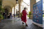 A woman walks past a poster showing how to avoid the spreading of COVID-19 as she arrives to vote at a polling station, in Rome, Sunday, Sept. 20, 2020. On Sunday and Monday Italians are called to vote nationwide in a referendum to confirm a historical change to the country's constitution to drastically reduce the number of Members of Parliament from 945 to 600. Eighteen million of Italian citizens will also vote on Sunday and Monday to renew local governors in seven regions, along with mayors in approximately 1,000 cities. (AP Photo/Andrew Medichini)