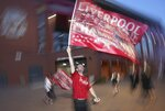 A Liverpool supporter celebrates outside Anfield Stadium in Liverpool, England, Thursday, June 25, 2020 after hearing Chelsea had scored in the English Premier League soccer match between Chelsea and Manchester City. Liverpool will be crowned Premier League champions if Manchester City fail to beat Chelsea. (AP Photo/Jon Super)