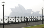 A jogger runs in the morning as smoke haze hangs over the Sydney Opera House in Sydney, Thursday, Nov. 21, 2019. The annual Australian fire season, which peaks during the Southern Hemisphere summer, has started early after an unusually warm and dry winter. (AP Photo/Rick Rycroft)