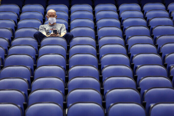 Mike Lemcke, from Richmond, Va., sits in an empty Greensboro Coliseum after the NCAA college basketball games were cancelled at the Atlantic Coast Conference tournament in Greensboro, N.C., Thursday, March 12, 2020. The biggest conferences in college sports all canceled their basketball tournaments because of the new coronavirus, seemingly putting the NCAA Tournament in doubt. The vast majority of people recover from the new coronavirus. According to the World Health Organization, most people recover in about two to six weeks, depending on the severity of the illness.  (AP Photo/Ben McKeown)