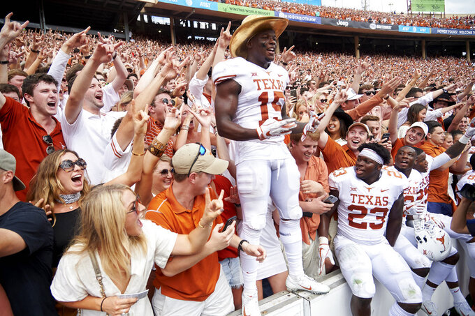 Texas defensive back Chris Brown (15) wears the Golden Hat and celebrates with fans after defeating Oklahoma 48-45 in an NCAA college football game at the Cotton Bowl, Saturday, Oct. 6, 2018, in Dallas. (AP Photo/Cooper Neill)