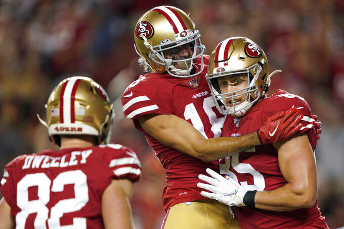 San Francisco 49ers tight end George Kittle, right, celebrates with Dante Pettis, center, and Ross Dwelley after scoring against the Cleveland Browns during the second half of an NFL football game in Santa Clara, Calif., Monday, Oct. 7, 2019. (AP Photo/Tony Avelar)