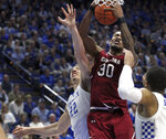 South Carolina's Chris Silva, center, pulls down a rebound between Kentucky's Reid Travis, left, and Keldon Johnson during the second half of an NCAA college basketball game in Lexington, Ky., Tuesday, Feb. 5, 2019. Kentucky won 76-48. (AP Photo/James Crisp)