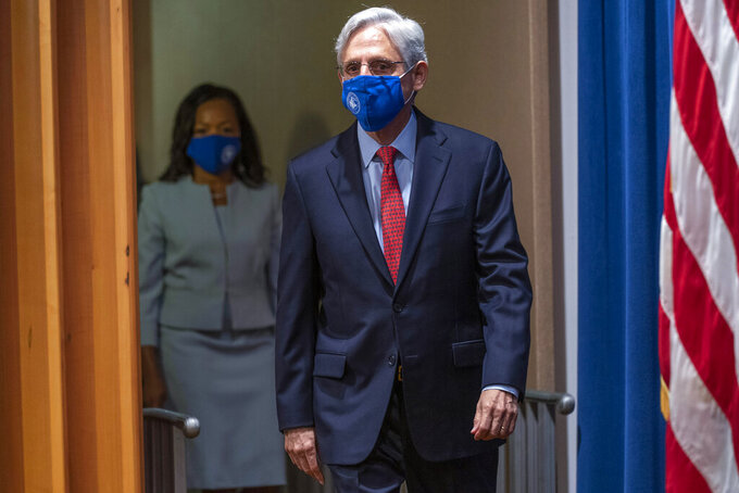Attorney General Merrick Garland and Assistant Attorney General for Civil Rights Kristen Clarke, left, arrives for a news conference at the Department of Justice in Washington, Thursday, Aug. 5, 2021, to announce that the Department of Justice is opening an investigation into the city of Phoenix and the Phoenix Police Department. (AP Photo/Andrew Harnik)