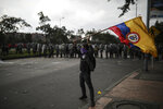 An anti-government protester waves a Colombia national flag during a protest in Bogota, Colombia, Thursday, Nov. 21, 2019. Colombia's main union groups and student activists called for a strike to protest the economic policies of Colombian President Ivan Duque government and a long list of grievances.  (AP Photo/Ivan Valencia)